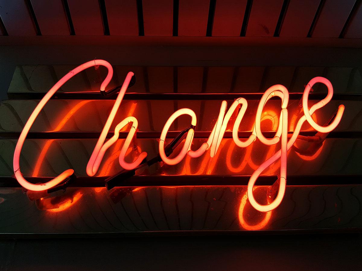 Rote Neonröhren auf dunklem Hintergrund in der Form des Wortes Change